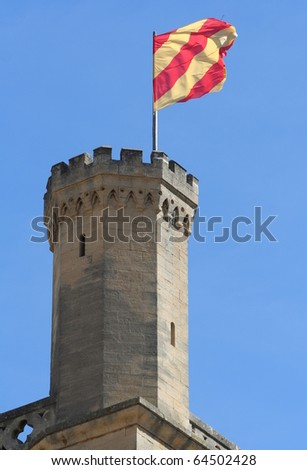 Red and yellow flag blowing in the wind on a tower of a castle located in the town of Uzes in southern France
