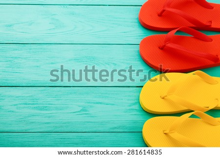 Red and yellow flip flops on blue wooden background. Summer accessories. - stock photo