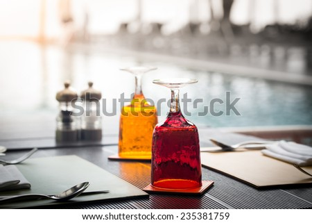Red and Yellow Glass of water on luxury table setting near swimming pool, selective focus with bokeh background  - stock photo
