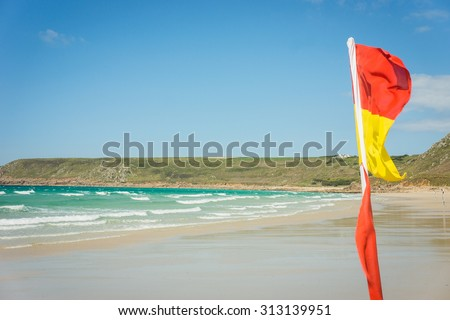 Red and Yellow lifeguard flag on British beach marking safe zone for swimming and surfing - stock photo