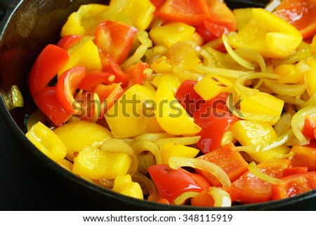 Red and yellow paprika with onions in a cast iron frying pan. Lovely fresh and tasteful combination for any dish. Reflections in the oily surface of the vegetables. - stock photo
