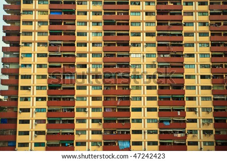 Red and Yellow Pattern of Windows and Balconies on High Rise Building in Kuala Lumpur - stock photo