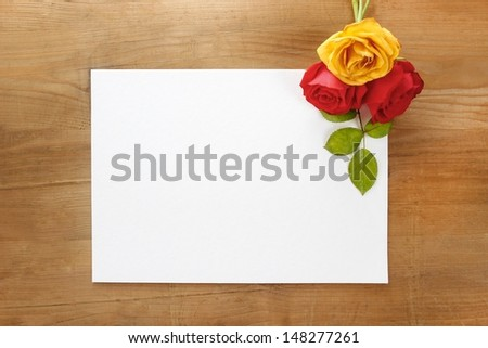 Red and yellow roses on wooden background. Blank sheet of paper, copy space. - stock photo
