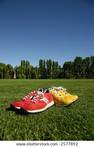 Red and yellow running shoes on a sports field with a deep blue sky - stock photo