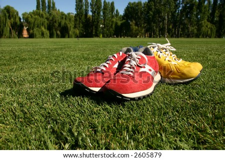Red and yellow running shoes on a sports field with a deep blue sky