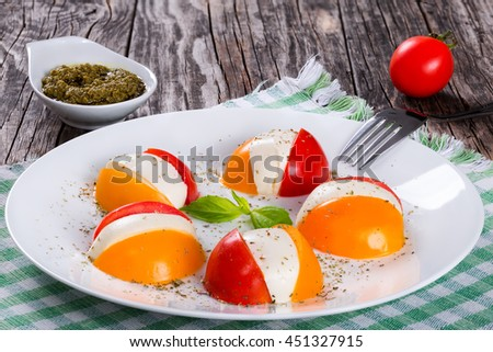 red and yellow tomatoes and mozzarella caprese salad on white dish sprinkled with dried herbs, sauce pesto on background, italian style, close-up - stock photo