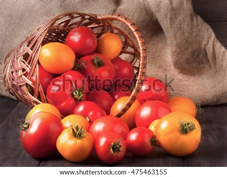 red and yellow tomatoes in a wicker basket on  wooden table
