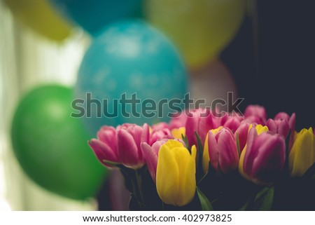 Red and yellow tulips on a background with balloons - stock photo