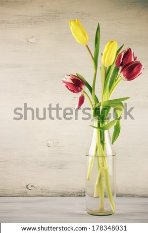 Red and yellow tulips on vintage wooden background.