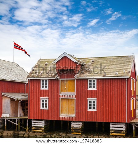Red and yellow wooden coastal house in Norwegian fishing village. Rorvik, Norway