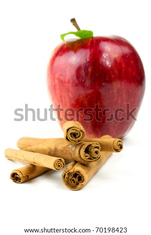Red apple and cinnamon  sticks isolated on white