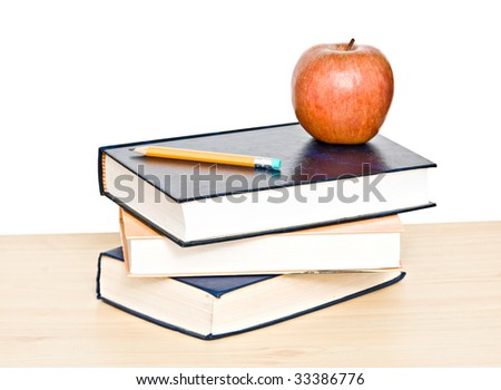 Red apple and pencil on top of books