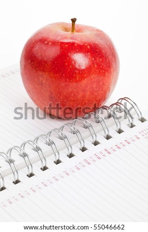 Red apple and Personal Organizer close up
