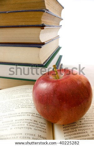 Red apple and pile of books. Photo close