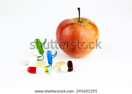 Red apple and pills capsules isolated. Concept of health in pills and fruits - stock photo