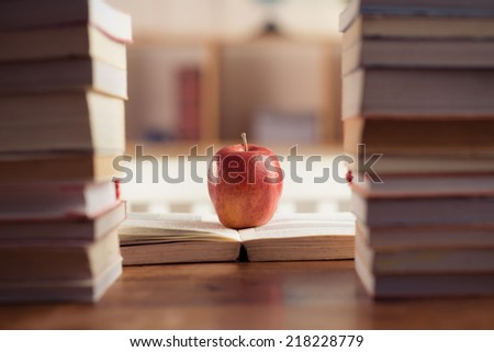 Red apple between book stacks as a symbol of wisdom - stock photo