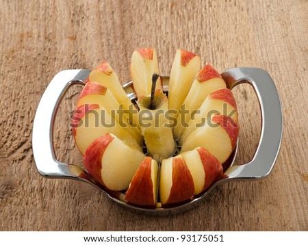 Red apple cut into slices with tool - stock photo