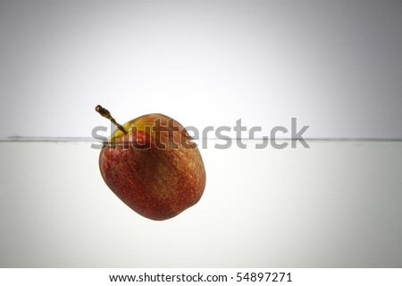 Red apple floating on water. - stock photo