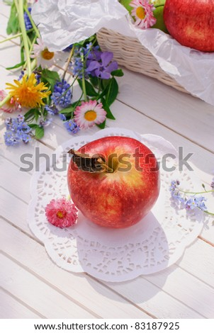 Red apple, flowers and basket on white garden table in sunny summer day