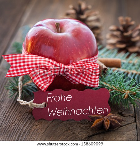 red apple for christmas with tag and german text frohe weihnachten - stock photo