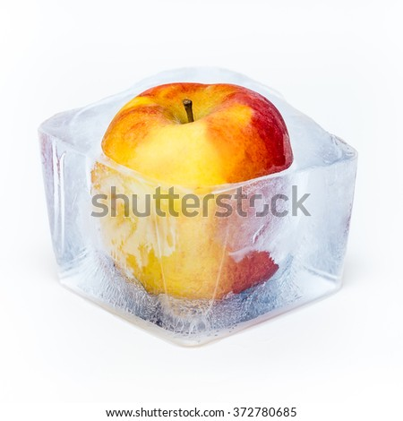Red apple frozen in the ice cube