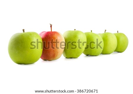 Red apple in a row of green apples isolated on white background with clipping path