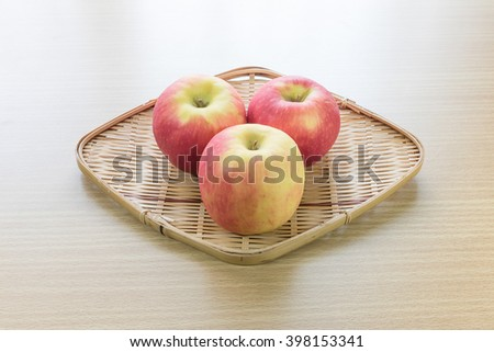 Red apple in basket on wooden background - stock photo