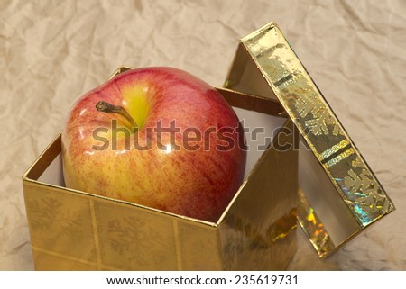 Red apple in golden box as a gift, close up - stock photo