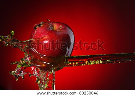 red apple in juice stream - stock photo