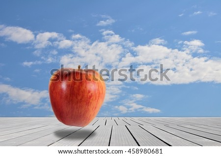 Red apple in surreal landscape with cloudy sky - stock photo