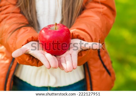 red apple in the children's hands in a park in autumn - stock photo