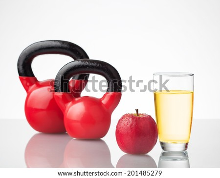 Red apple, juice, and kettlebells on reflective surface. - stock photo