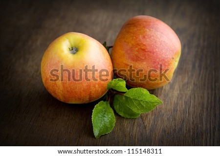 Red apple lying on a dark brown table. - stock photo