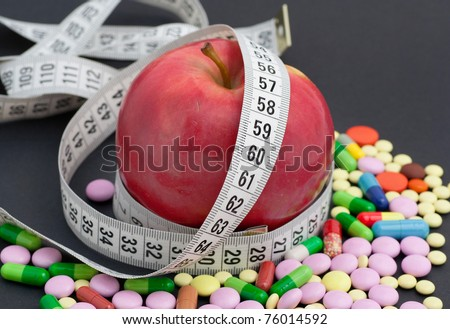 red apple, meter and pill - stock photo