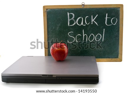 red apple on a laptop computer in front of an old blackboard - stock photo