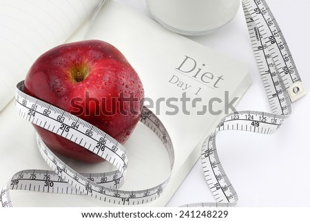 Red apple on a notebook and measuring tape, Diet concept. - stock photo