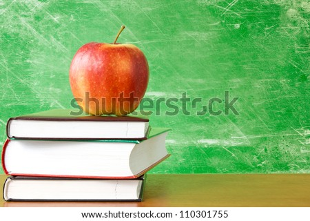 red apple on a pile of books against dirty chalkboard - stock photo