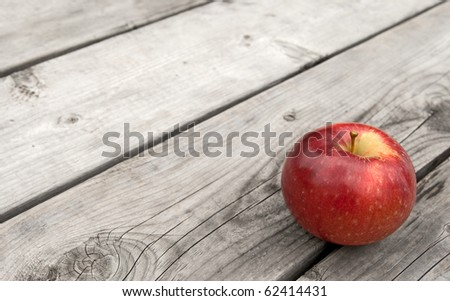 Red apple on gray old wooden table, with copy space. - stock photo