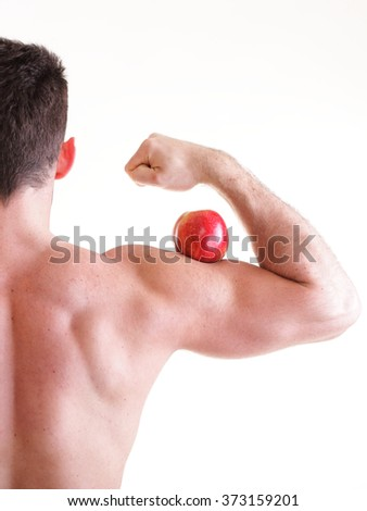 Red apple on man bicep muscle isolated on white. Athletic sexy male body builder holding fruit on arm back view