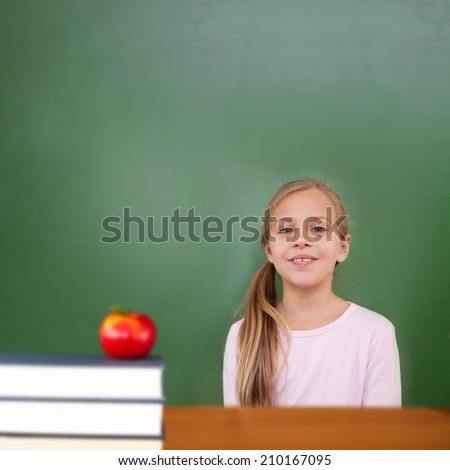 Red apple on pile of books against cute pupil - stock photo