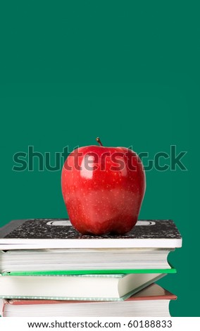 Red apple on top of notebook and stack of textbooks with blackboard on the background.  Concept of education or back to school. - stock photo