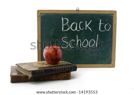 red apple on two old books in front of an old blackboard - stock photo