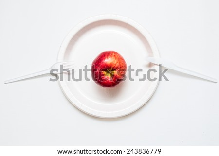 Red apple on white plate with knife and fork - stock photo