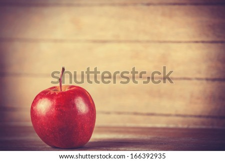 red apple on wooden table. Photo in retro color style. - stock photo