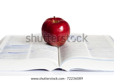 Red  apple placed on the top of the  book. - stock photo