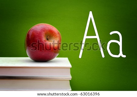 red apple placed on the top of white books, letter A written in the background. - stock photo