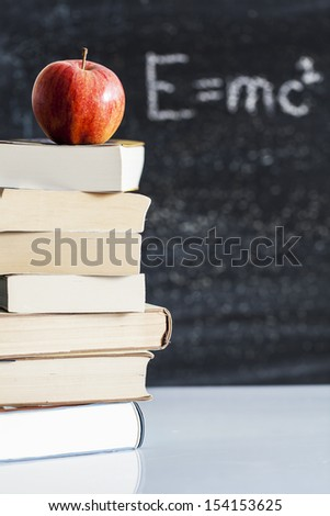 red apple resting on the book with chalk board as background - stock photo