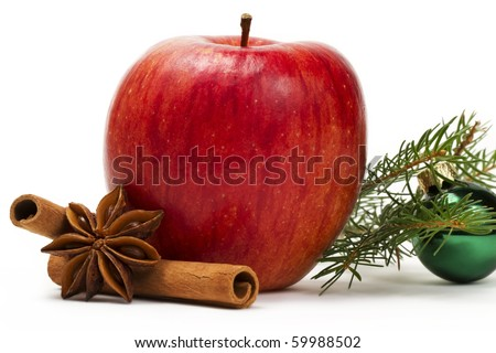red apple, star anise, cinnamon sticks, a green christmas ball and a branch on white background