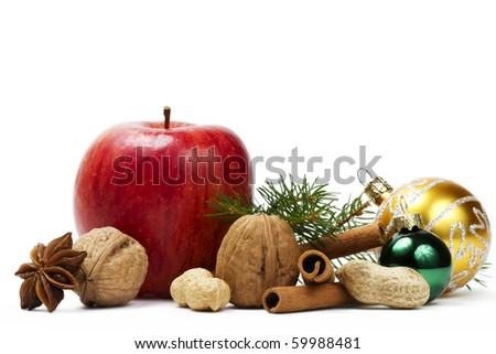 red apple, star anise, some nuts, golden and green christmas balls and a branch on white background - stock photo