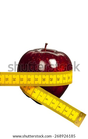 red apple surrounded  by metric tape